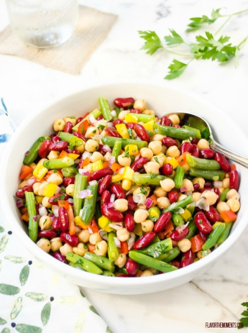 Three bean salad in white bowl with spoon