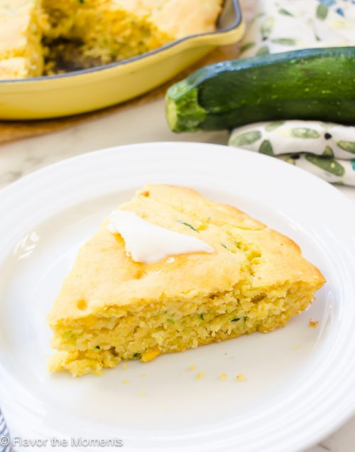Wedge of zucchini cornbread with pat of butter on top