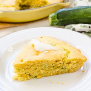 Zucchini cornbread on white plate with butter on top