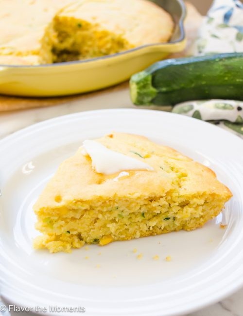Zucchini cornbread on a plate with butter on top