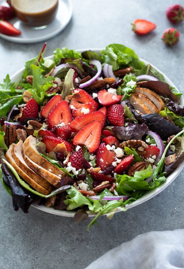 strawberry fields salad in a bowl with sliced strawberries and chicken on top