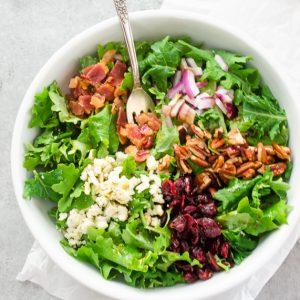 baby kale salad in white bowl