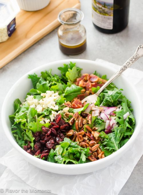 Baby kale salad in white bowl with fork