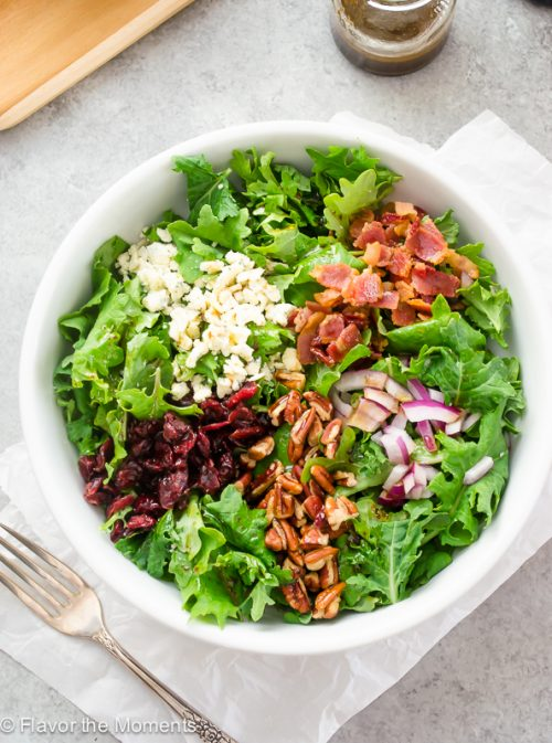 Baby kale salad in white bowl with bacon and cranberries