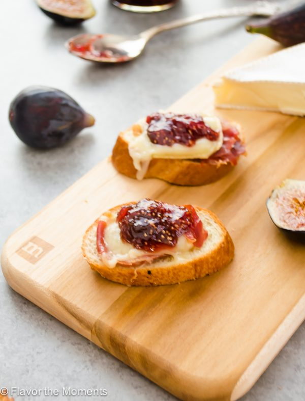 Brie and fig crostini on a cutting board