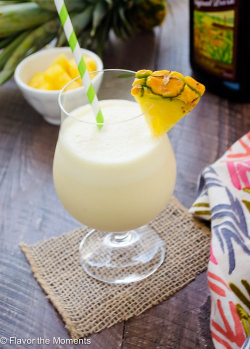 Fresh pineapple pina colada in glass with pineapple wedge on rim