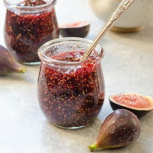 fig jam in a jar with spoon and fresh figs alongside