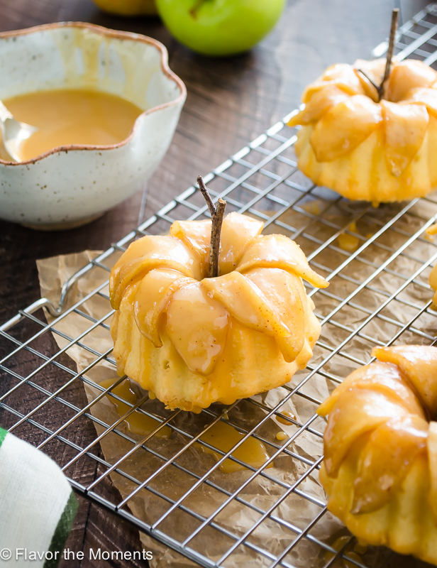 Mini caramel apple pound cakes on wire rack with caramel sauce in background