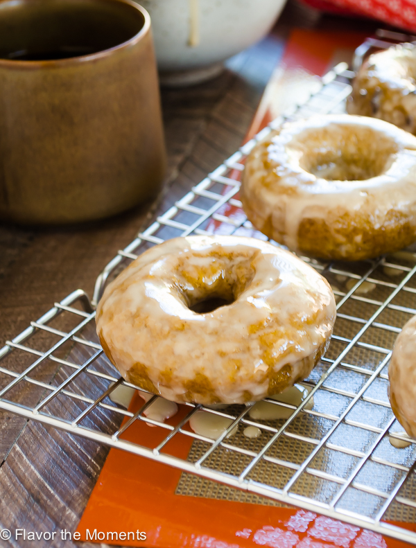 baked pumpkin donuts on a wire rack with coffee cup