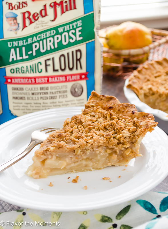 slice of pear crumble pie on white plate with bag of flour behind it