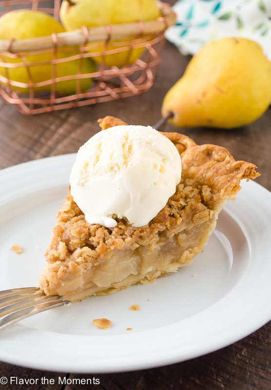 slice of pear crumble pie on white plate with ice cream on top