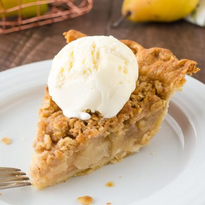 Pear Ginger Crumble Pie is an easy flaky pie crust filled with a fresh ginger pear filling and topped with a spiced oatmeal crisp topping!