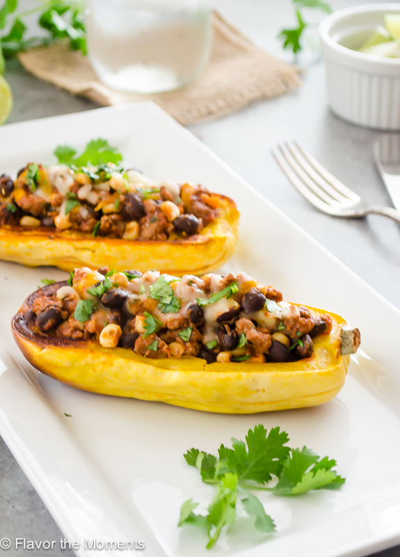 close up of chili stuffed delicata squash on serving platter with forks alongside