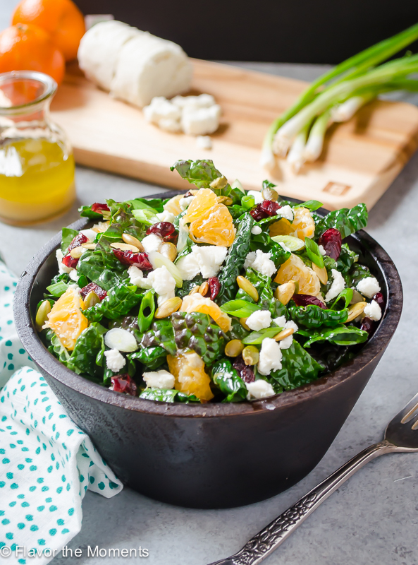 Citrus Kale Salad in bowl with dressing and ingredients on a cutting board