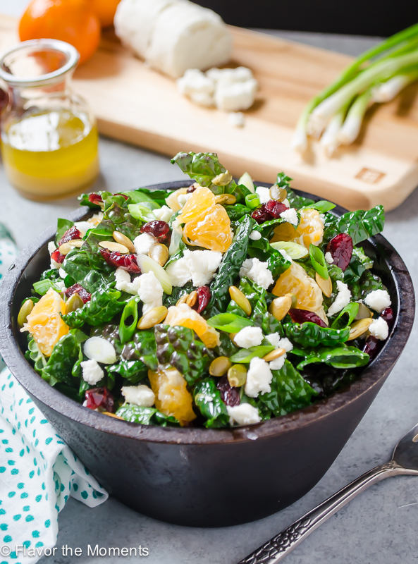 close up of citrus kale salad in a bowl with dressing in background