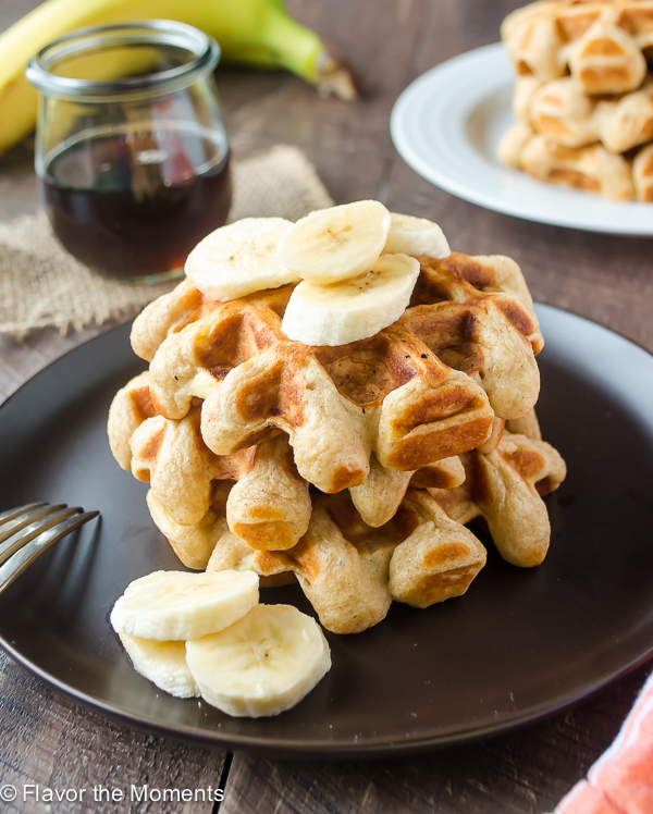 Stack of banana waffles on plate with bananas on top