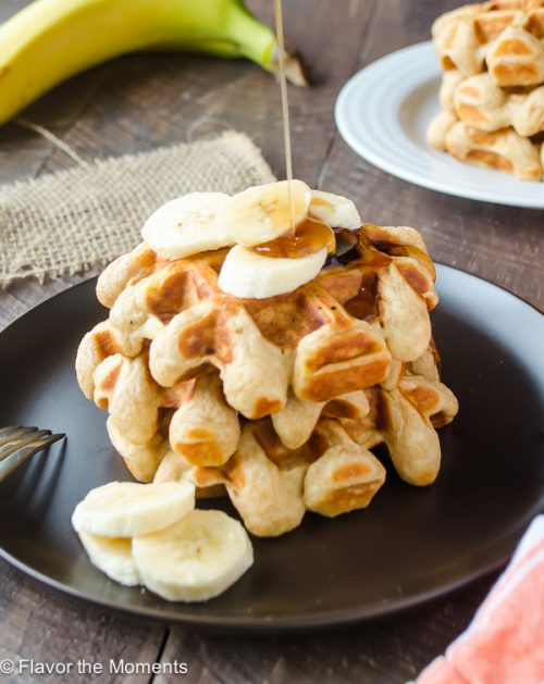 Stack of banana waffles on plate with bananas and maple syrup drizzled over top