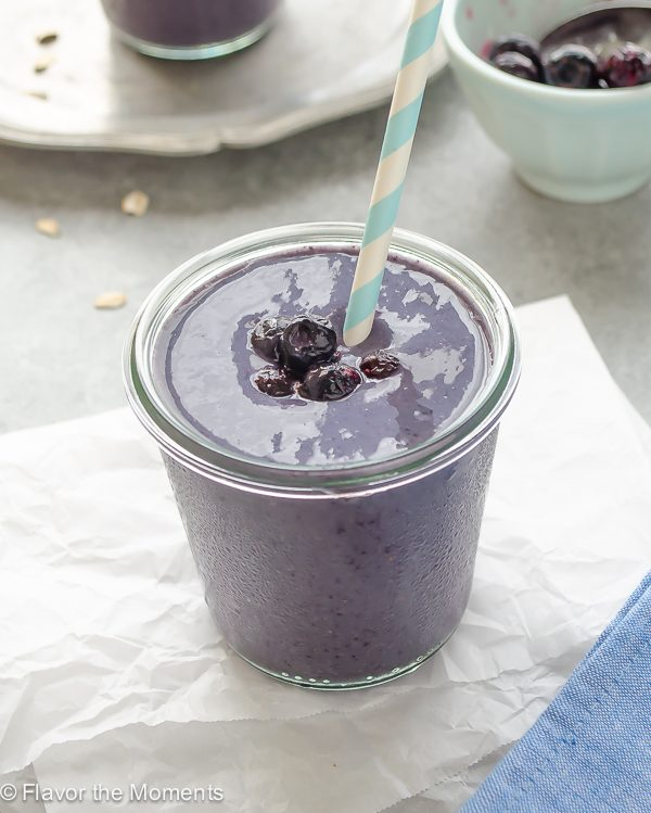 Blueberry banana smoothie in jar with blueberries on top