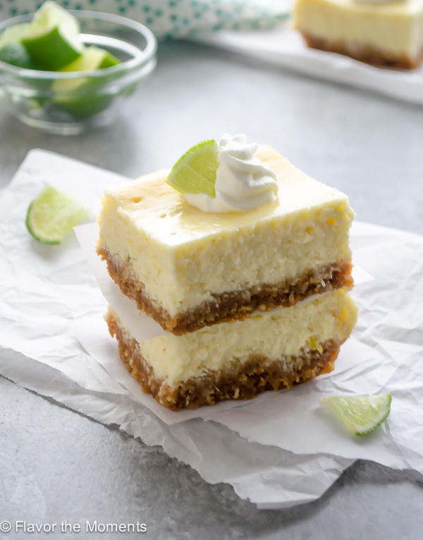 key lime cheesecake bars stacked up on parchment paper