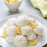 Meyer lemon Greek butter cookies or  kourabiedes on white plate with lemon slices