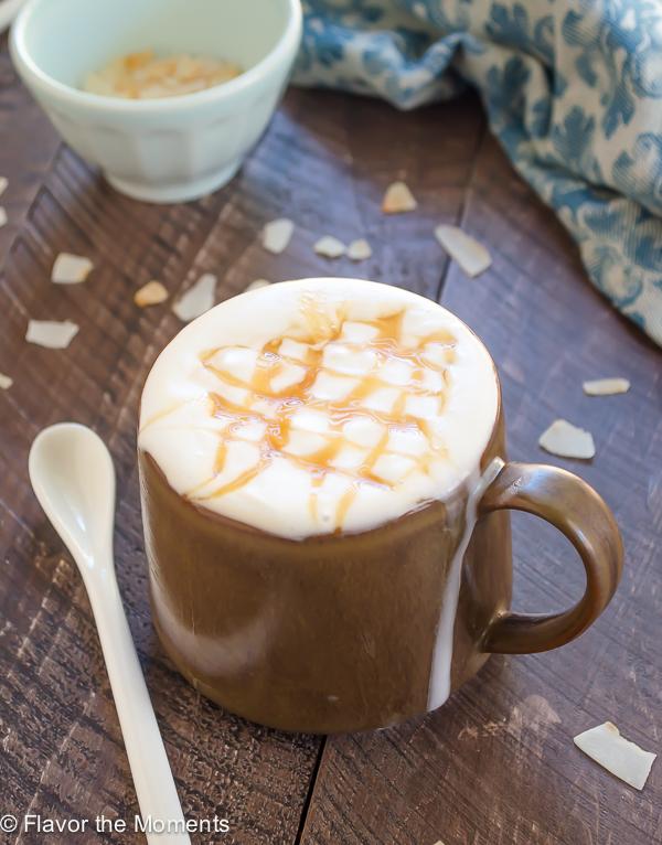 mug of coconut milk macchiato topped with coconut whipped cream