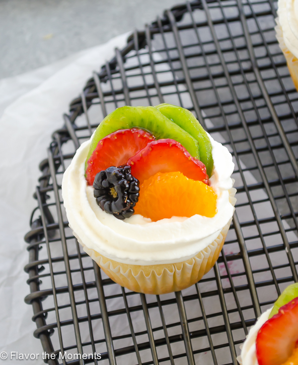 Close up of fruit tart vanilla cupcakes on wire rack