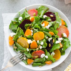 plate of roasted beet salad on parchment paper with fork