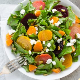 Roasted beet salad in white bowl with fork