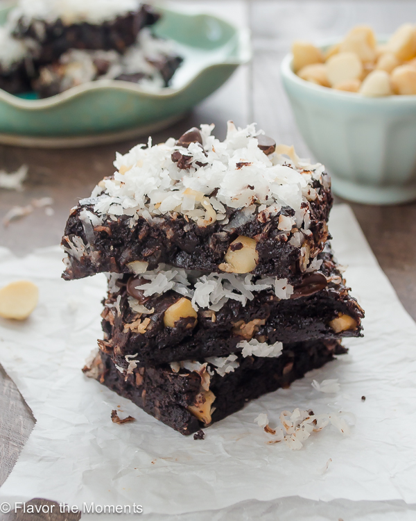 coconut oil brownies stacked on parchment paper with macadamia nuts and coconut