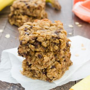 Three peanut butter banana chocolate chip oat bars stacked on parchment