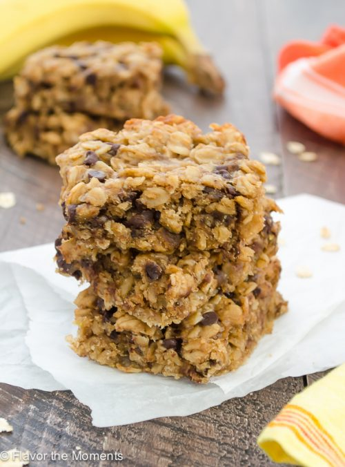 close up of Peanut Butter Banana Chocolate Chip Oat Bars stacked up on parchment paper