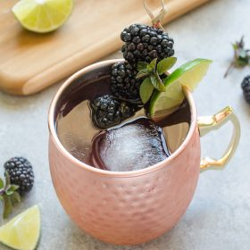 Blackberry moscow mule in copper mug with lime and blackberries
