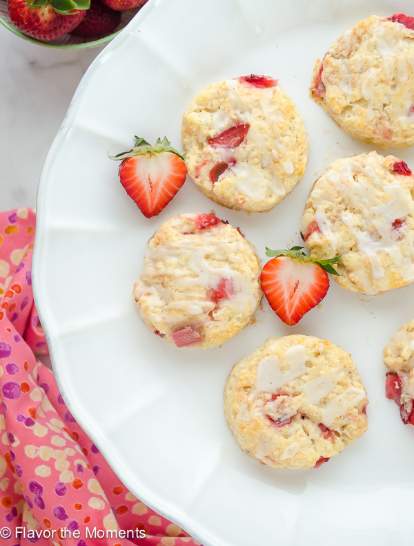 overhead shot of strawberry scones on white cake stand with fresh strawberries