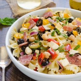 Italian pasta salad in white bowl with basil