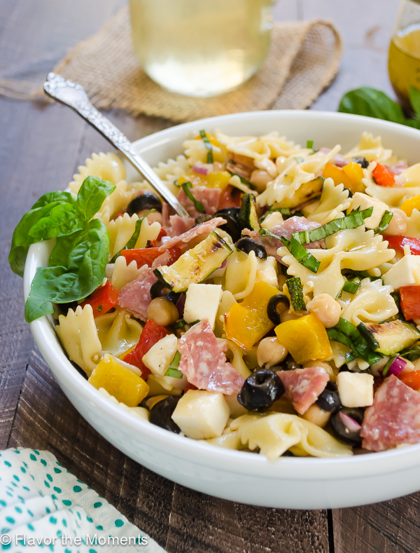 Italian pasta salad in white bowl with basil and spoon