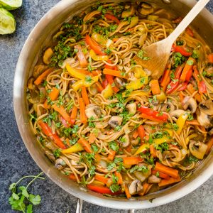 thai peanut veggie pasta in skillet with wooden spoon