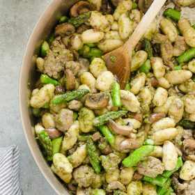 Pesto gnocchi in skillet with asparagus and mushrooms