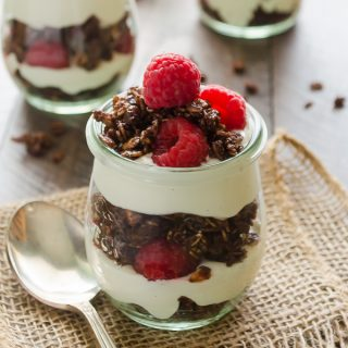 Chocolate Raspberry Cheesecake Yogurt Parfaits are layers of no bake Greek yogurt cheesecake, double chocolate granola, and fresh raspberries. They're perfect for breakfast or snacks! @FlavortheMoment