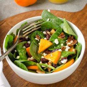Persimmon and Spinach Salad is baby spinach tossed with sweet persimmon, dried cranberries, goat cheese, pecans and a maple orange vinaigrette!