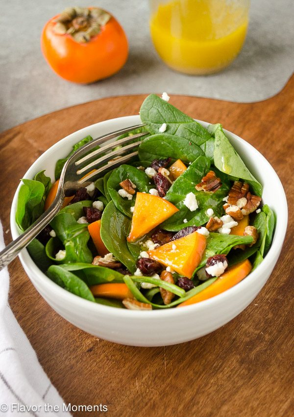 Persimmon and Spinach Salad is baby spinach tossed with sweet persimmon, chewy dried cranberries, creamy goat cheese, and crunchy pecans in an orange maple vinaigrette. It's a delicious fall salad that's perfect for holidays!