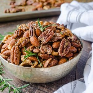 Roasted nuts in silver bowl with rosemary