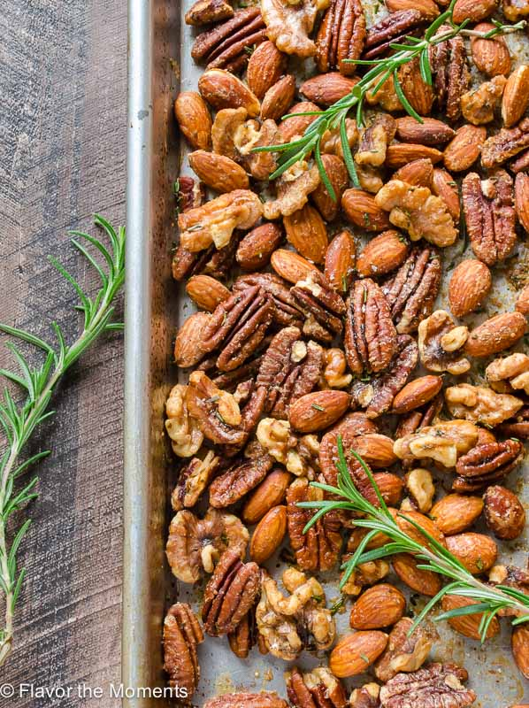 Spicy maple roasted nuts on baking sheet with rosemary