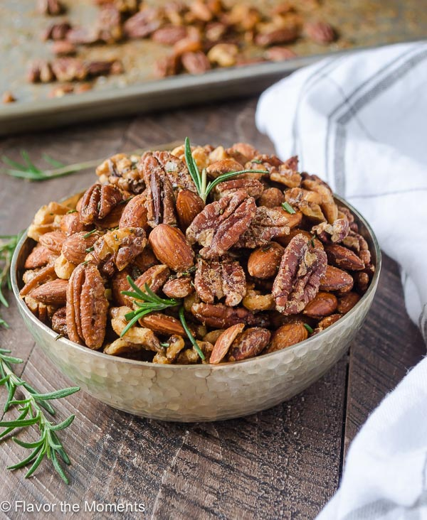 Spicy maple roasted nuts in bowl with rosemary