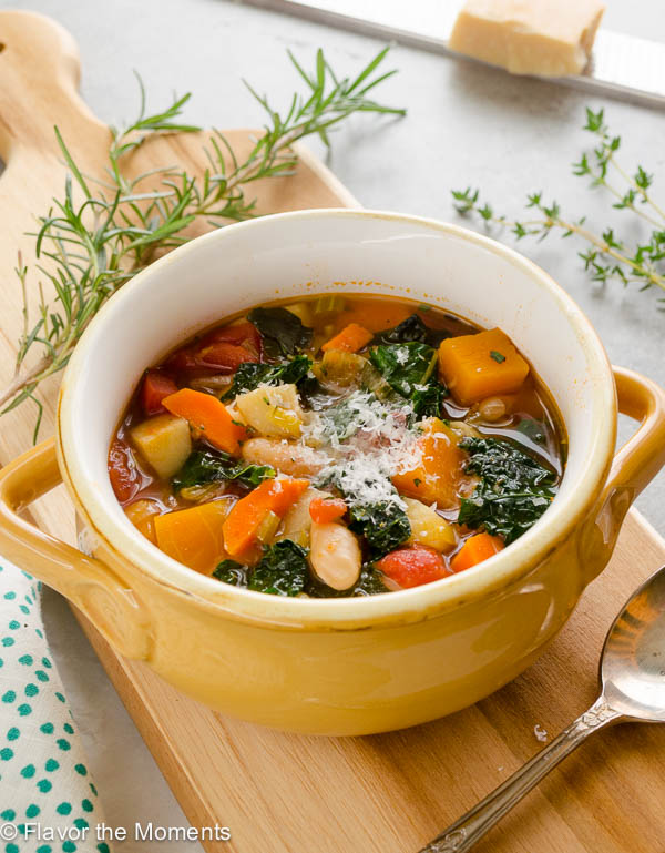 Autumn vegetable soup in a bowl with rosemary and parmesan on top