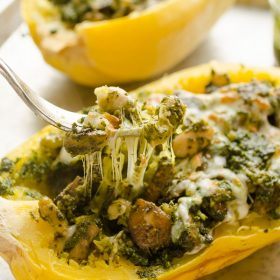 Cheesy Pesto Vegetarian Spaghetti Squash Boats are spaghetti squash halves stuffed with sauteed mushrooms, white beans, kale pesto, and plenty of cheese. This is lightened up comfort food at it's best! @FlavortheMoment