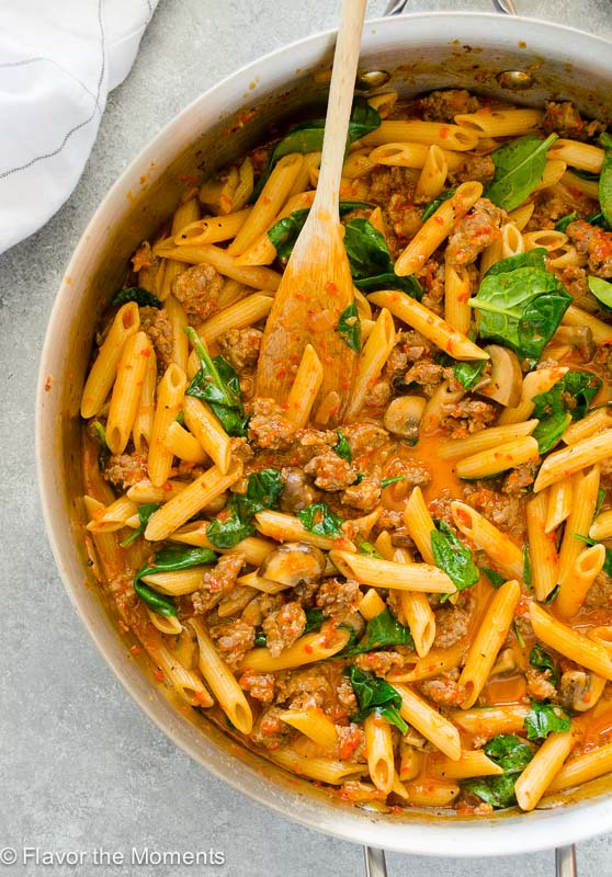 Red pepper pasta in skillet with wooden spoon
