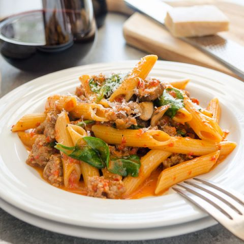 Creamy sausage red pepper pasta on plate with fork