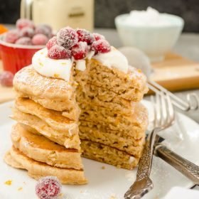 Fluffy Cranberry Orange Eggnog Pancakes are amazingly fluffy whole grain pancakes made with eggnog. They're topped with whipped cream and orange sugared cranberries for one special holiday breakfast! @FlavortheMoment