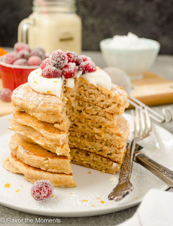 eggnog pancakes stacked up with whipped cream and cranberries