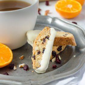 Cranberry orange biscotti on plate with mug of tea